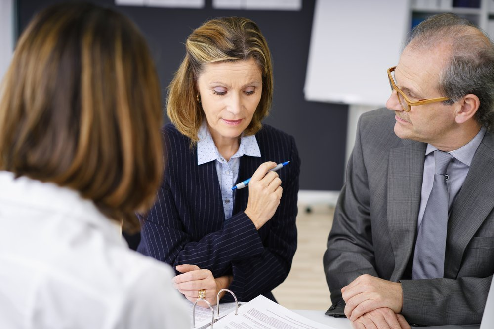 Middle-aged couple planning for retirement in a meeting with a female broker or investment adviser in her office